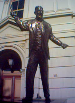 John Curtin in bronze, holding up a roll of paper